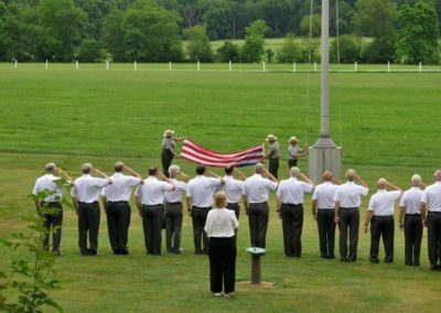 The West Point Alumni Glee Club salutes as the flag is folded