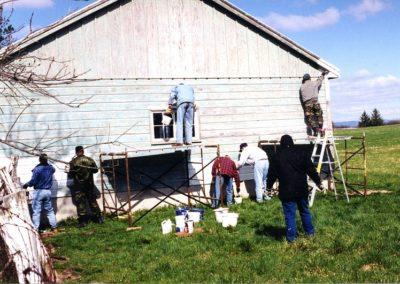 USS Eisenhower crew members paint a barn at Eisenhower farm